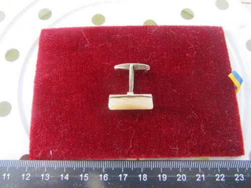 Запонка серебряная с камнем.