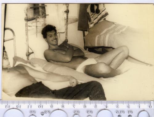 Аматорское фото советского периода, изображающее двоих мужчин, лежащих на железных кроватях.