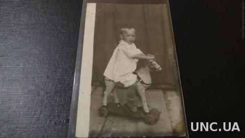 Фото открытка . Девочка с игрушками. Лошадка  на колесах.
