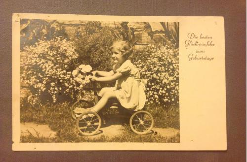 Старинная фотооткрытка. Девочка за рулём веломашинки.