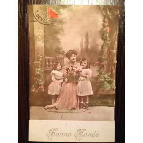 Французская фотооткрытка. С Новым годом! Женщина с букетом и девочками в саду.